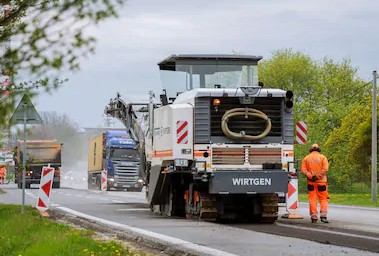 Milling machine removes old asphalt from the road